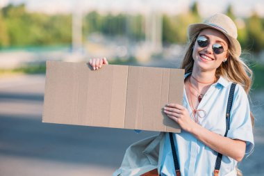 smiling woman with cardboard hitchhiking