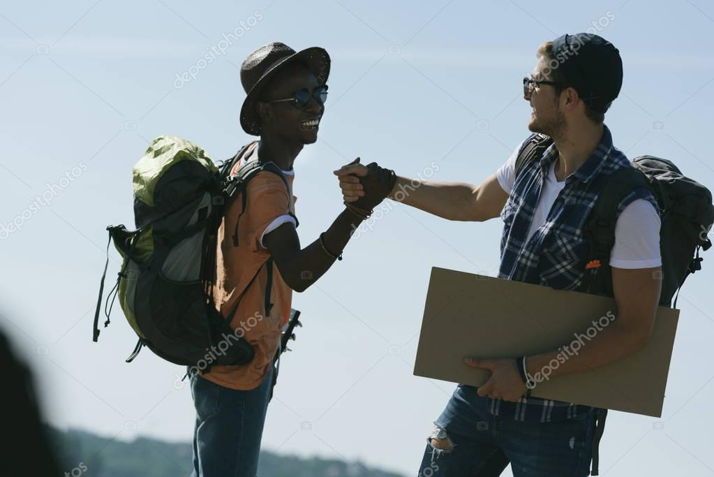 multicultural hitchhikers shaking hands