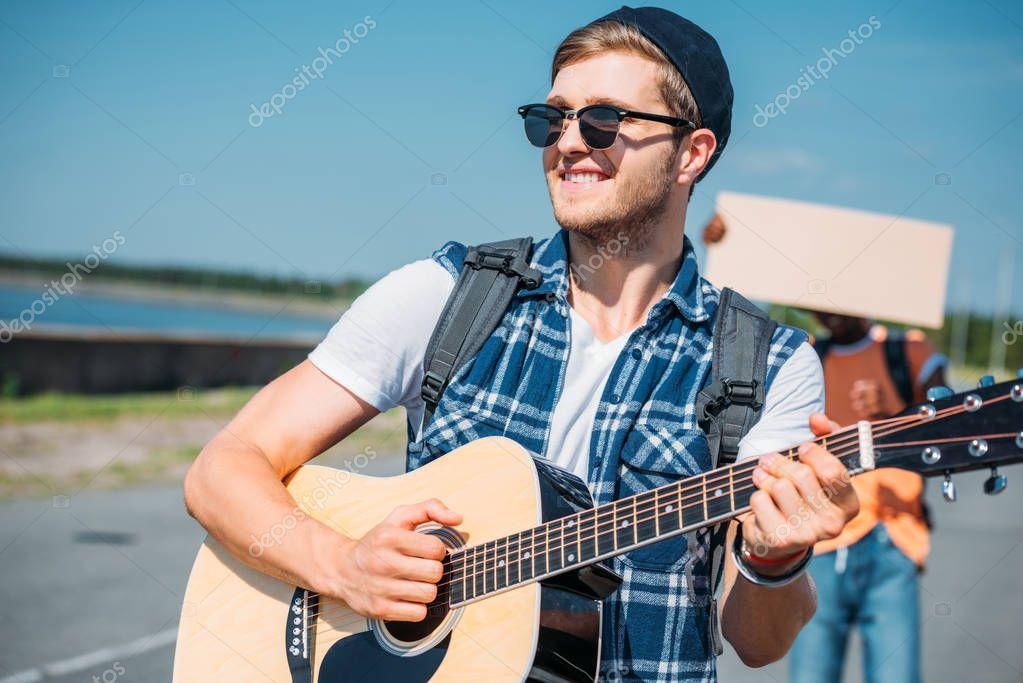 caucasian man playing guitar