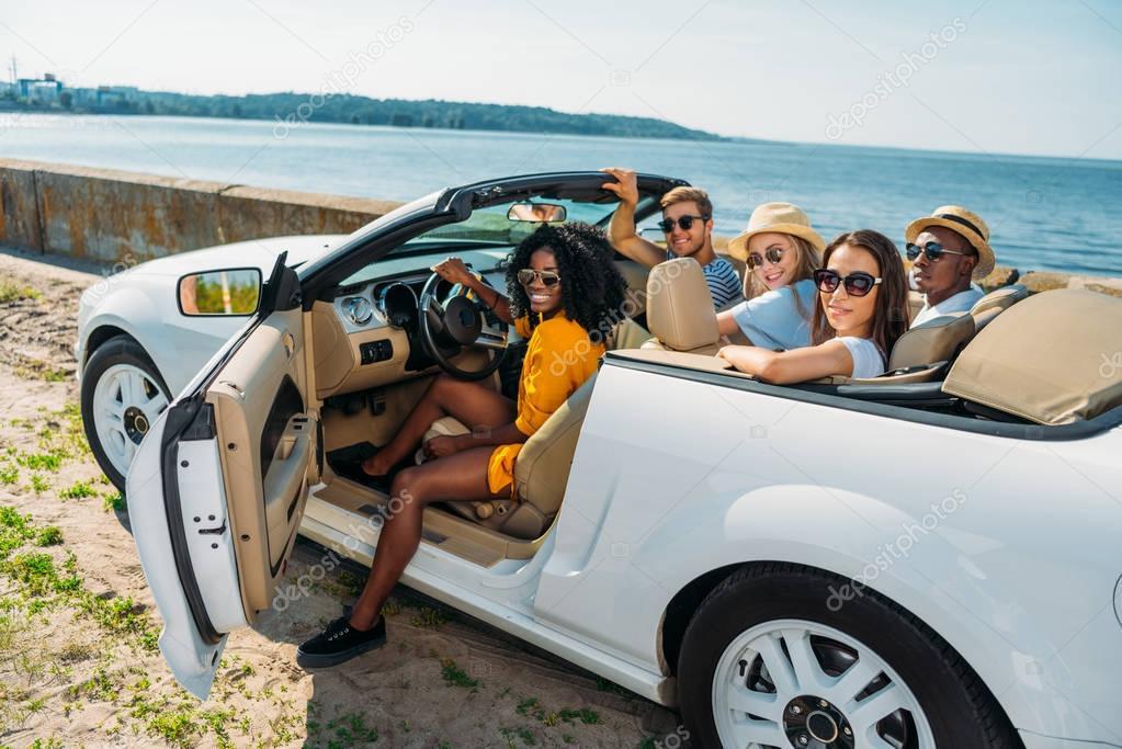 multicultural friends in car at seaside