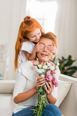 Daughter covering mothers eyes