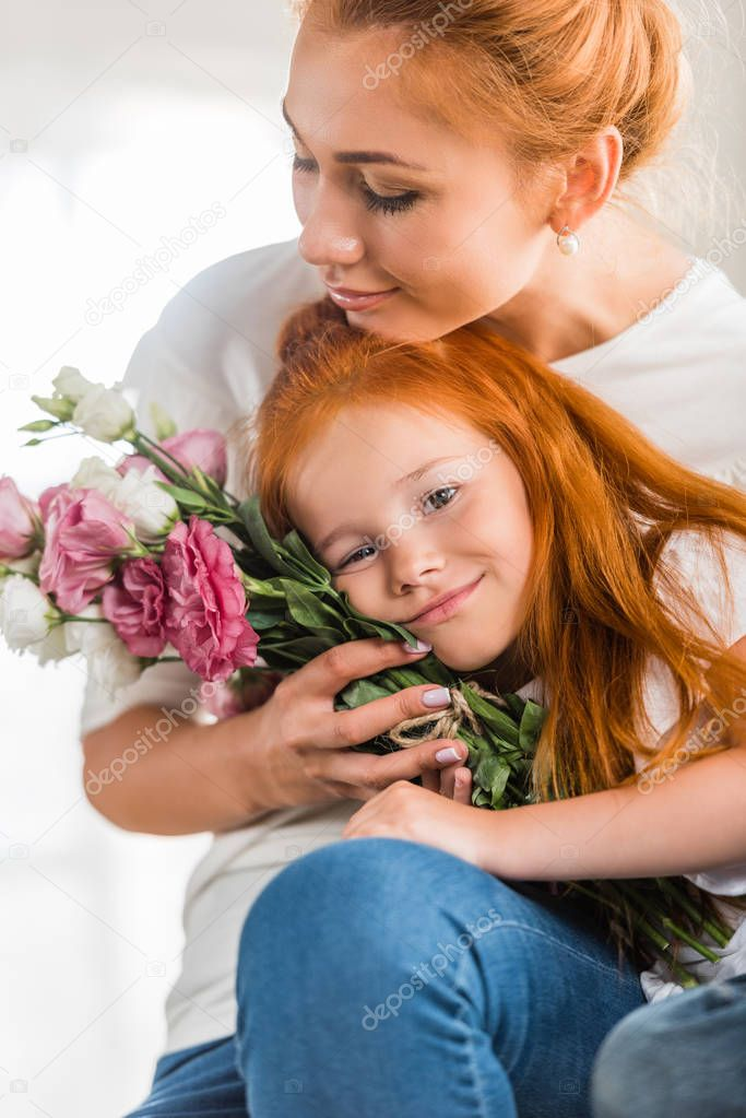 mother with flowers hugging little daughter