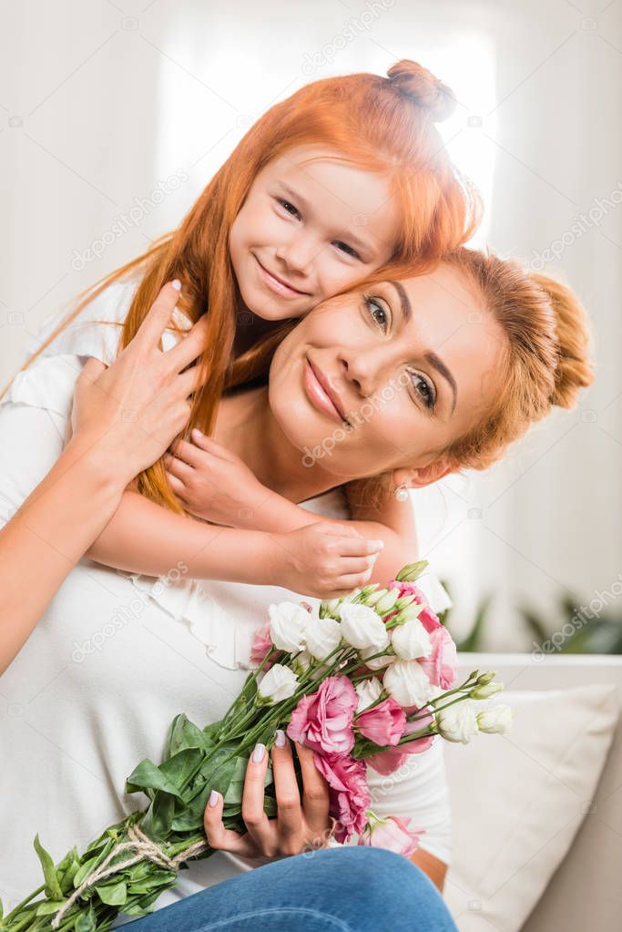 happy mother with flowers and daughter