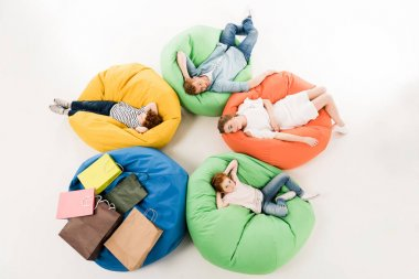family on bean bag chairs after shopping