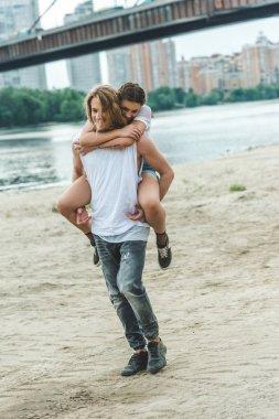 Young beautiful woman piggybacking on boyfriend on beach stock vector