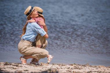mother and daughter hugging at seashore