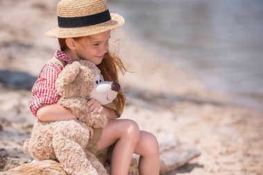 Child with teddy bear at seashore