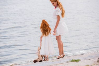 mother and daughter with teddy bear at seashore
