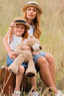 mother and daughter with suitcase and teddy bear