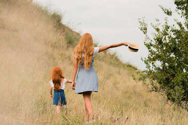 Mother and daughter walking on grass