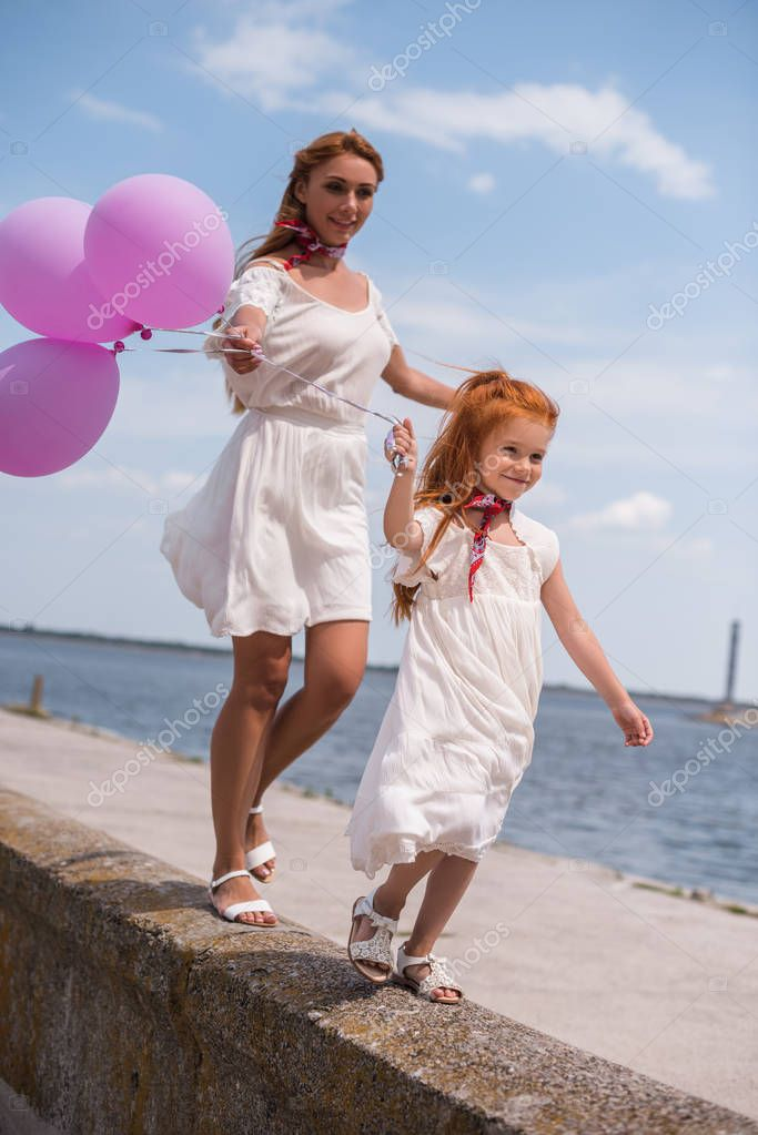 mother and daughter with balloons at seashore