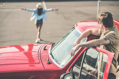 man in car looking at woman