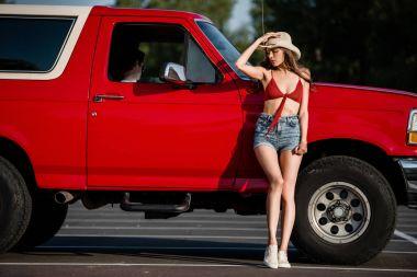 woman posing next to classical car