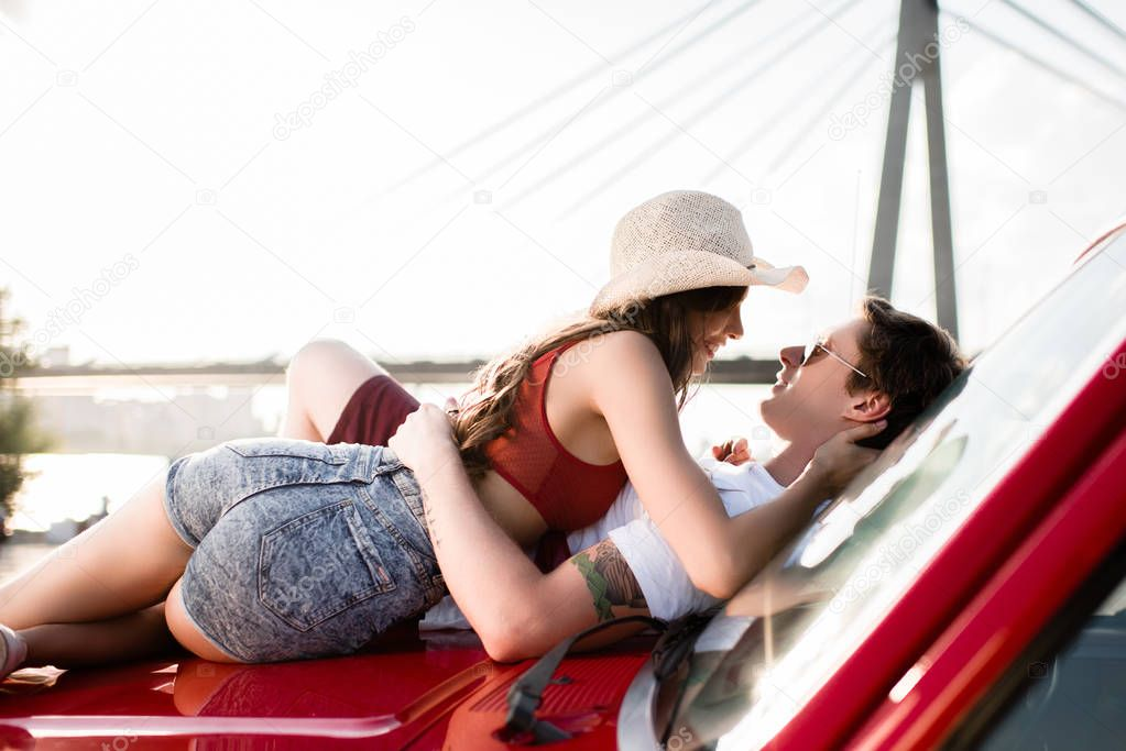 young couple lying on car