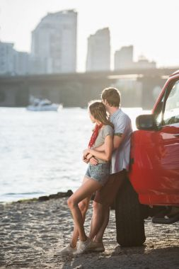 young couple hugging near car