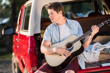 man playing guitar on car trunk