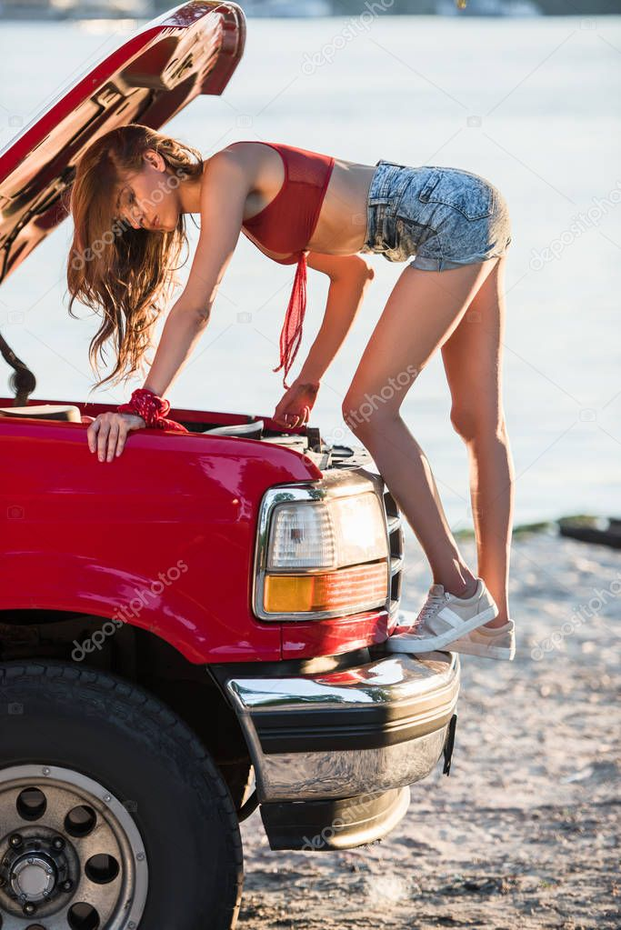girl fixing car engine
