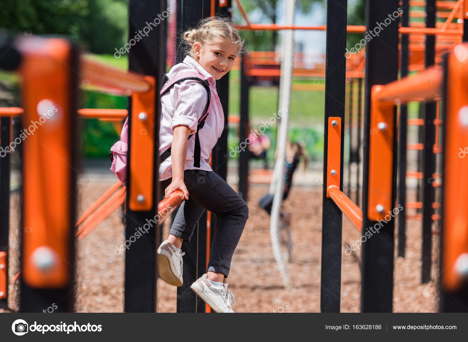 fb0ea1c2b0c Beautiful little girl with backpack smiling at camera while sitting on  playground — Photo by ArturVerkhovetskiy