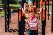 Rothaarige Kind auf Spielplatz