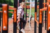 Schulkind mit Rucksack auf Spielplatz