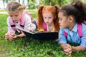 mnohonárodnostní děti čtení knihy na trávě