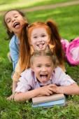 Fotografie mnohonárodnostní školačky s knihami v parku