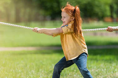 Redhead child pulling rope