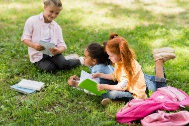 multiethnic schoolgirls studying on grass