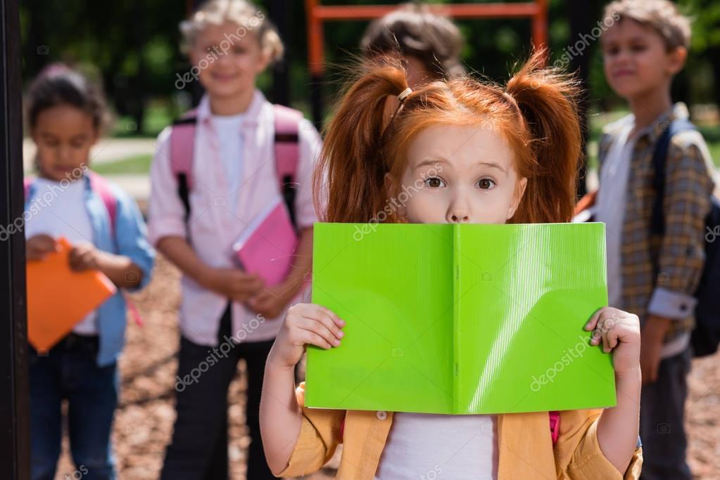 Adorable little redhead girl holding book and looking at camera while friends standing behind stock vector
