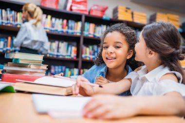 Happy little schoolgirls gossiping at library stock vector