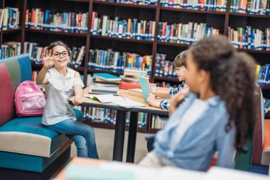 beautiful schoolgirls greeting at library