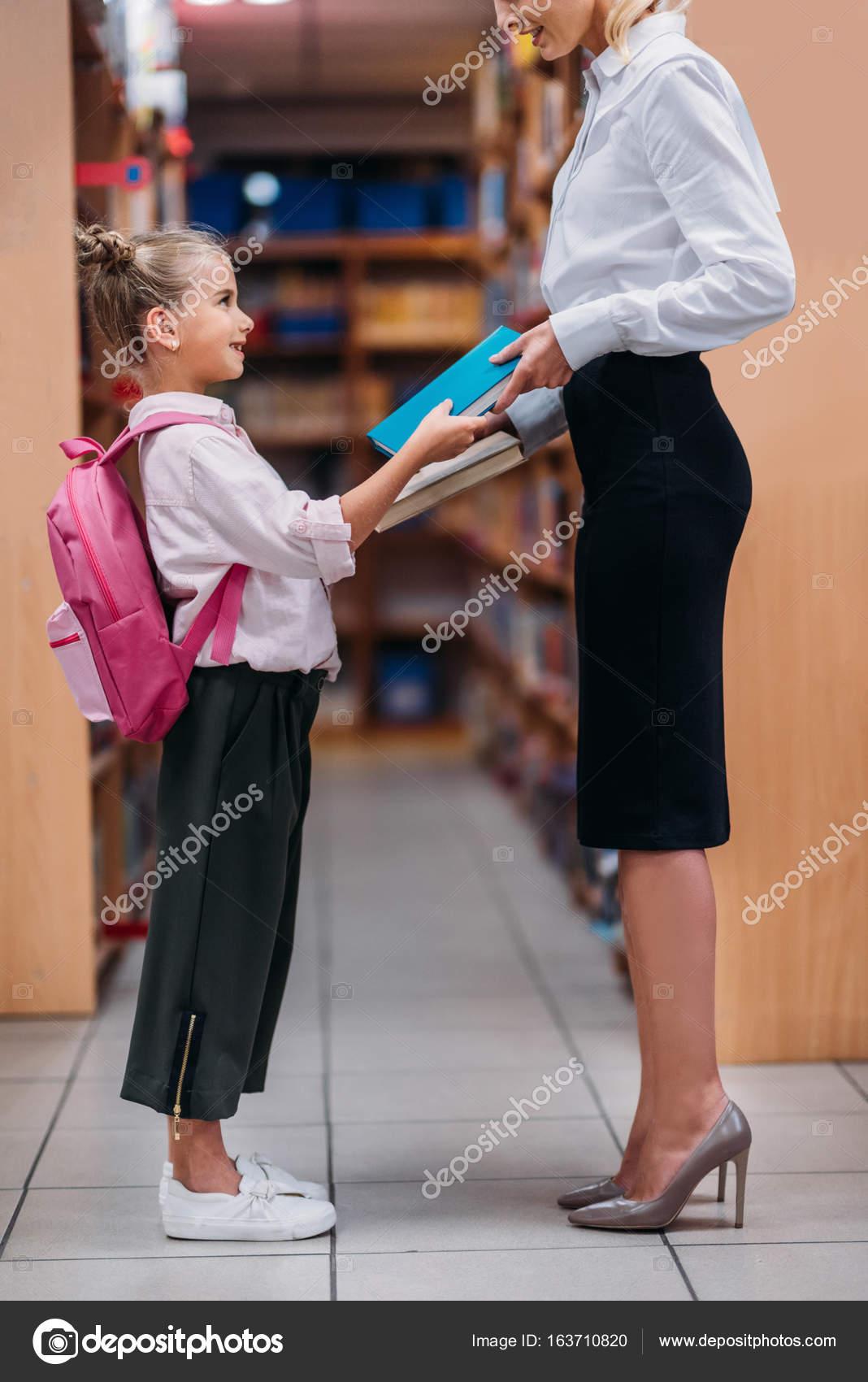 Teacher Giving Books To Schoolgirl Stock Photo