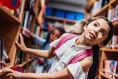 Fotografie školačky hledat knihy v knihovně