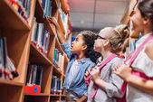 školačky hledat knihy v knihovně