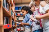 Schulmädchen suchen Bücher in Bibliothek