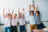 Fotografie Kinder mit erhobenen Händen neben whiteboard