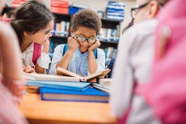 Adorable little kids in school library stock vector