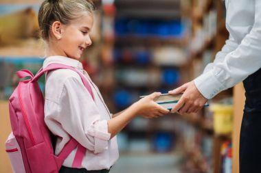 teacher giving books to schoolgirl