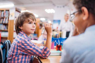 Adorable multiethnic schoolboys talking at library stock vector