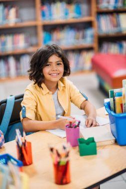 Cute african american schoolgirl doing homework in library stock vector