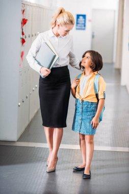 teacher and schoolgirl walking together