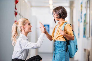 Teacher giving high five to adorable schoolgirl in school corridor stock vector