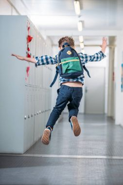 boy jumping in school corridor