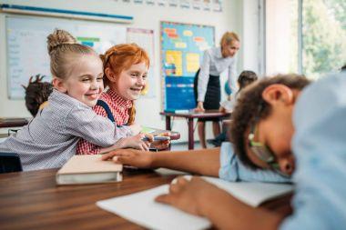 schoolgirls laughing of sleeping classmate