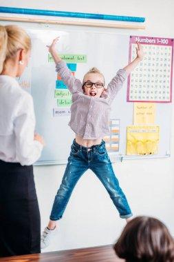 Teacher looking at jumping schoolgirl