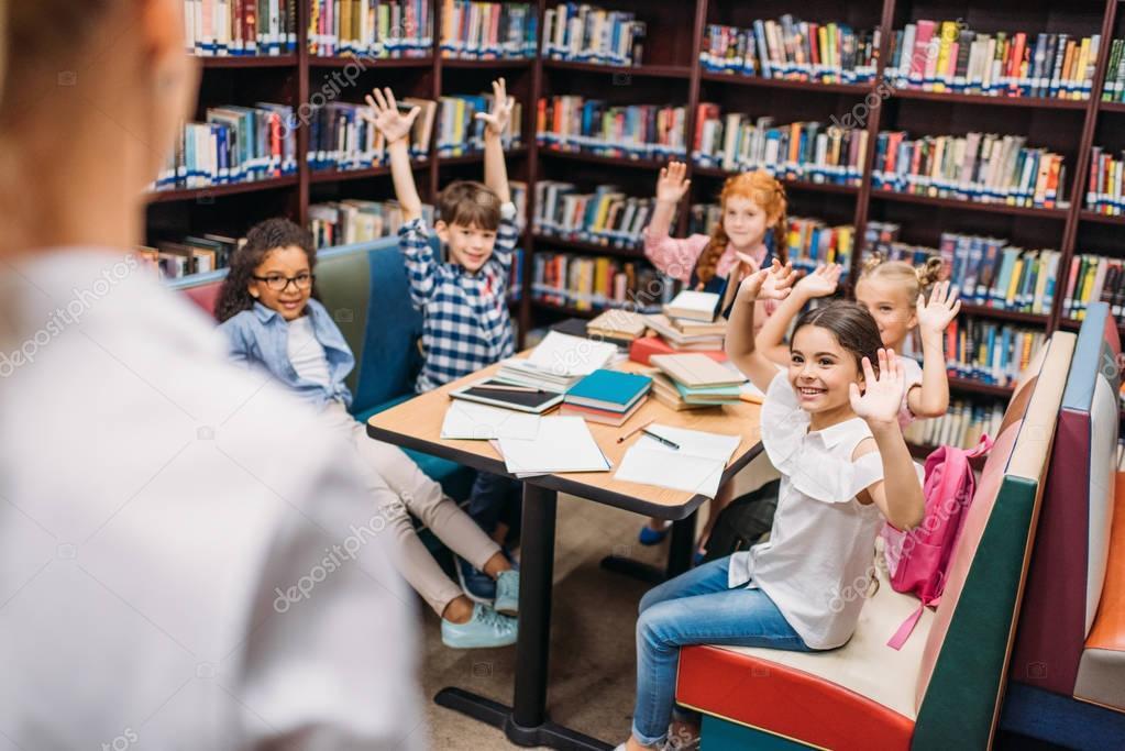 Adorable little kids raising hands in library stock vector