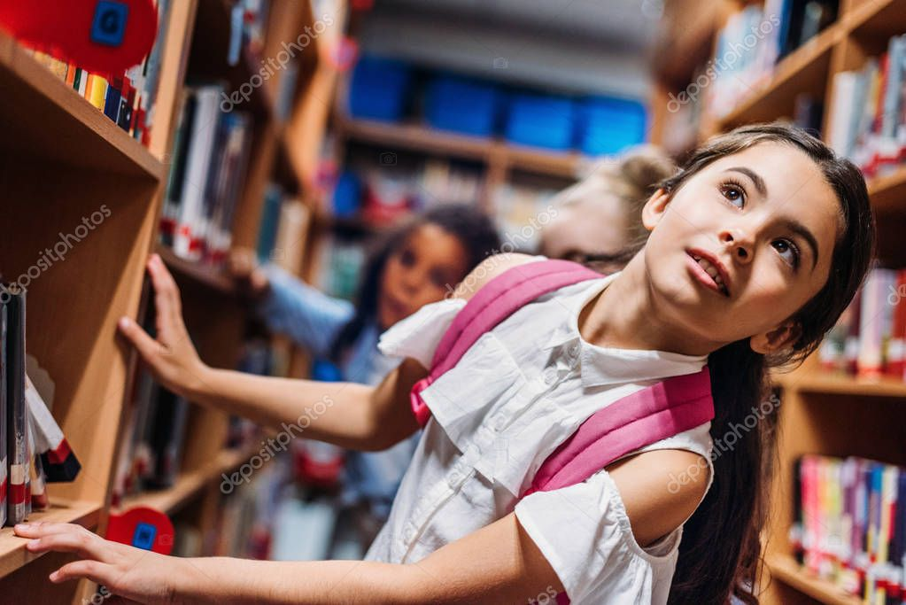 schoolgirls looking for books in library