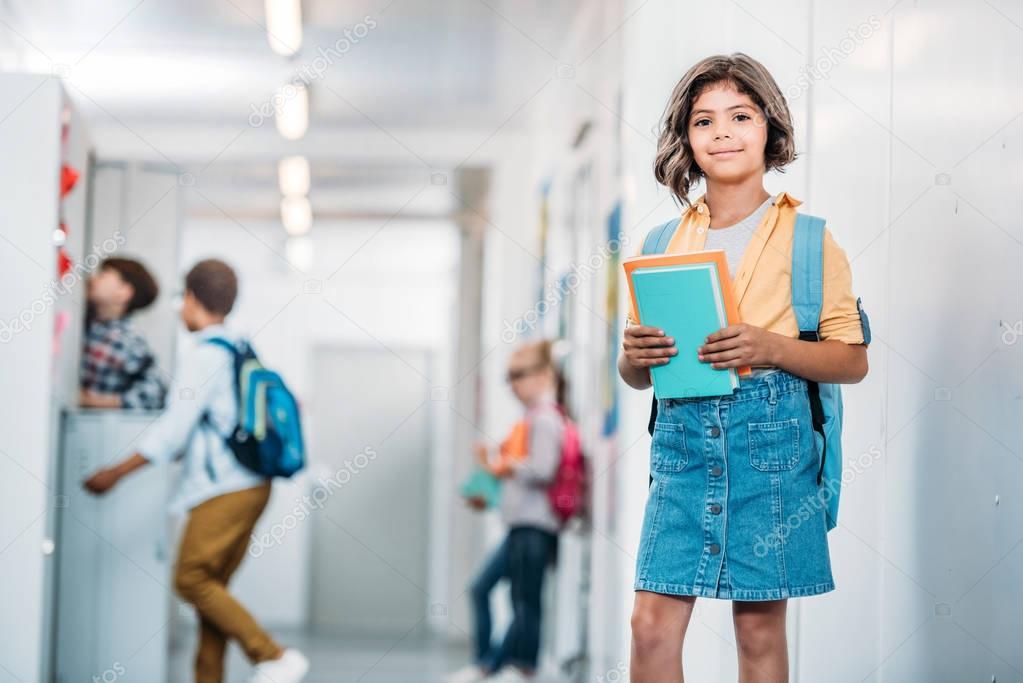 schoolgirl with books in corridor