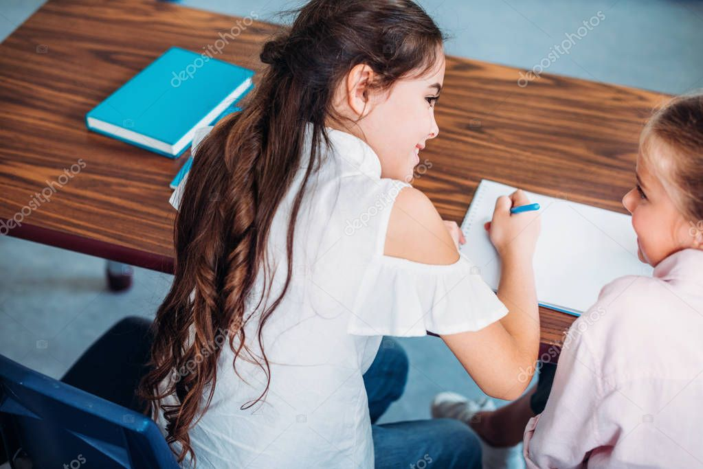 schoolgirls talking while sitting at desk
