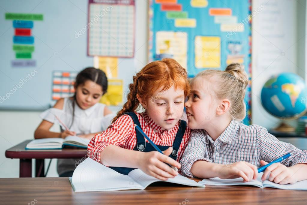 little girls gossiping in class